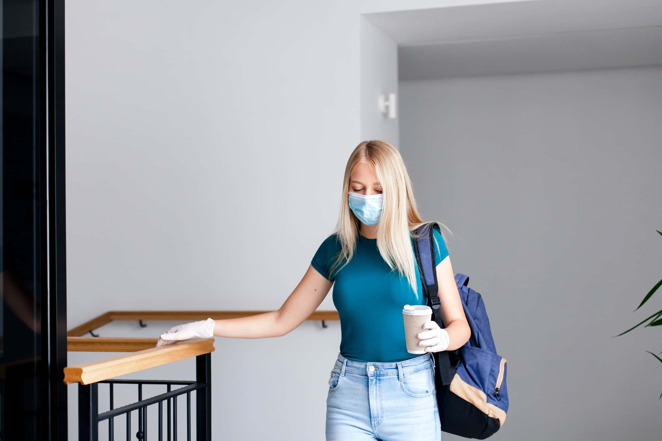 woman holds coffee cup while wearing gloves and mask