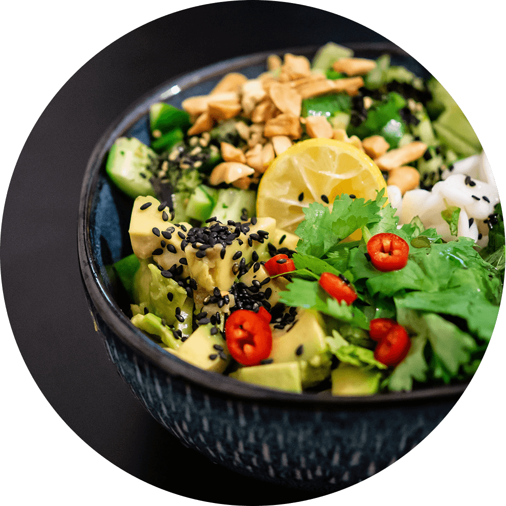 Bowl of salad filled with leafy greens, parsley, peppers, lemon, seeds, squash, avocado, and more