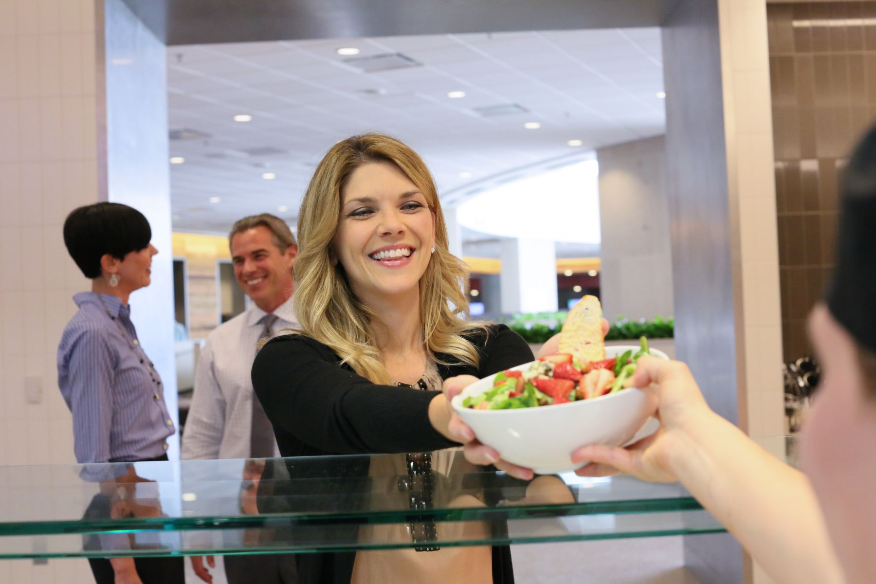 Guest receives salad from food service employee