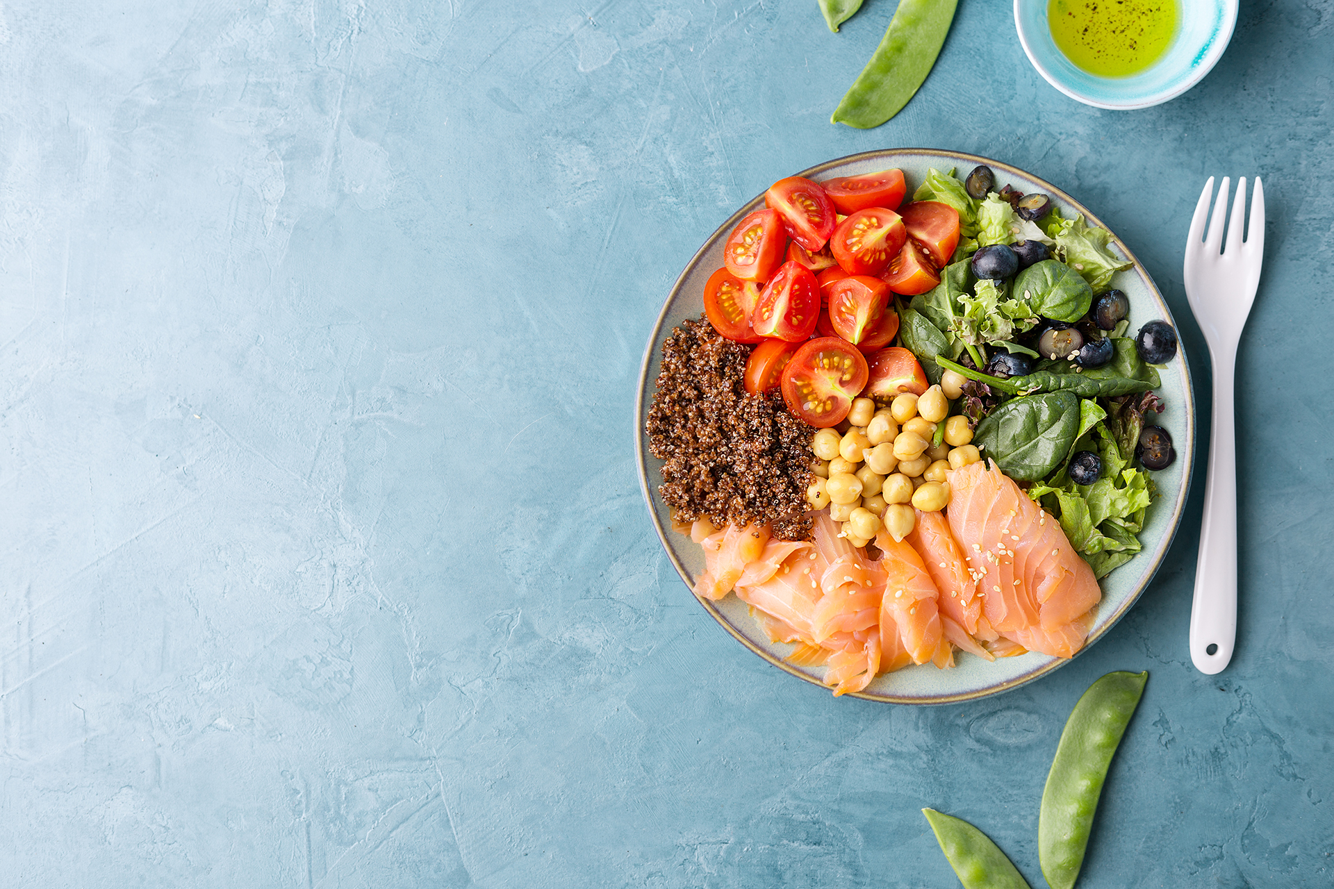 Buddha bowl salad with fish, salad leaves, quinoa, chickpea and spinach on blue table. Healthy Clean eating Detox Concept. Top View
