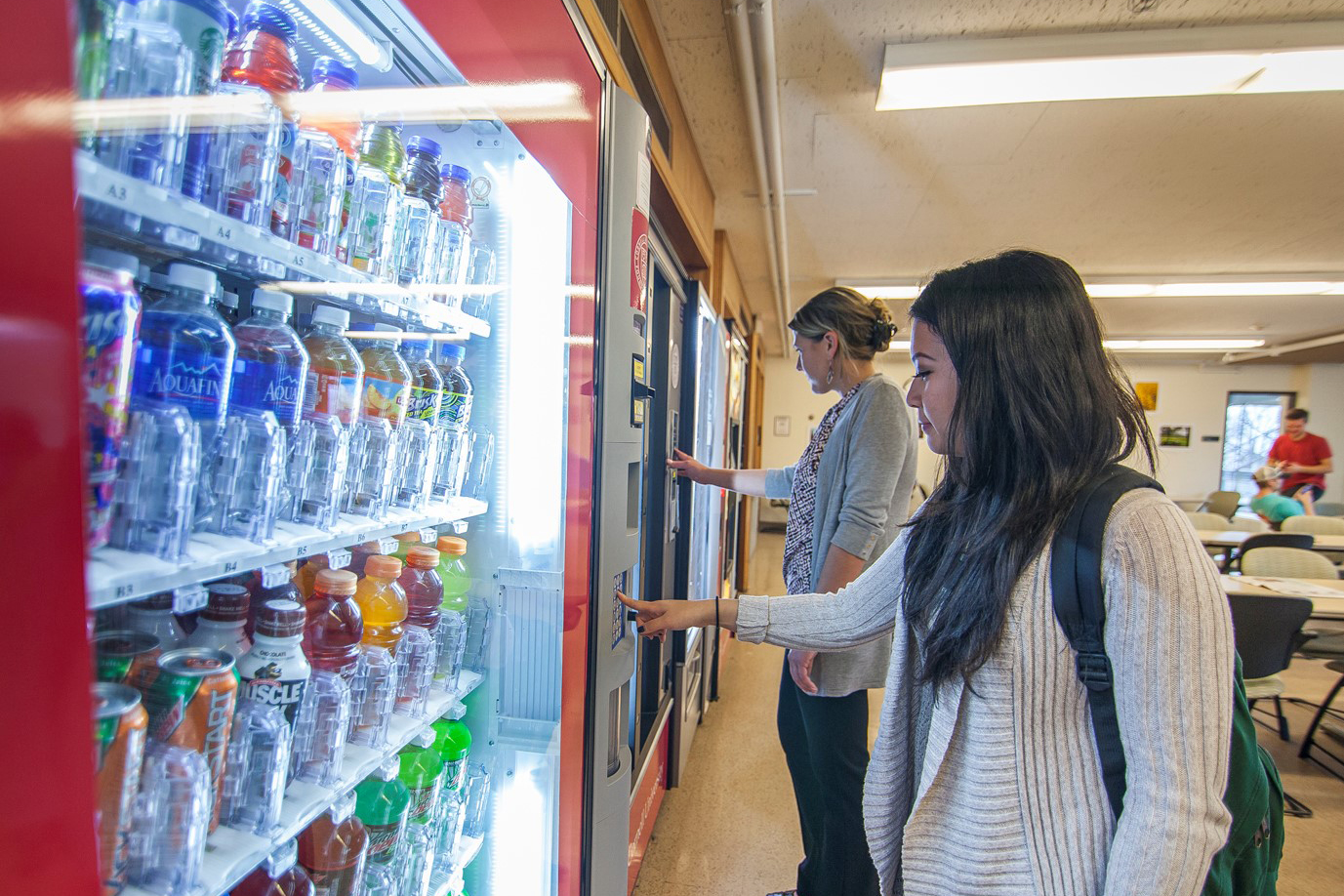 two women spend break time getting snacks and drinks from vending machines